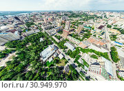 Купить «Aerial city view with crossroads and roads, houses, buildings, parks and parking lots. Sunny summer panoramic image», фото № 30949970, снято 21 января 2020 г. (c) Александр Маркин / Фотобанк Лори