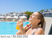 Купить «Safe sunbathing. Woman by the pool on vacation», фото № 30950050, снято 18 июля 2019 г. (c) Светлана Кузнецова / Фотобанк Лори