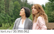 Купить «Two women, young and elderly, are looking into the distance and are talking against the backdrop of mountains and forests. Network marketing, female friendship, mothers day, mother and daughter», видеоролик № 30950062, снято 9 июня 2019 г. (c) Ольга Балынская / Фотобанк Лори