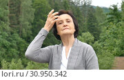 Купить «Beautiful elderly woman against the backdrop of the mountain forest straightens her hair with her hand. Pensioners travel, happy old age, social concept, mother's day», видеоролик № 30950342, снято 13 июня 2019 г. (c) Ольга Балынская / Фотобанк Лори