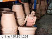 Купить «Woman chooses pots clay pots in store warehouse», фото № 30951254, снято 21 августа 2019 г. (c) Яков Филимонов / Фотобанк Лори