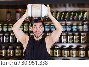 Купить «Bodybuilder holding big pot of sport supplements over head in store», фото № 30951338, снято 28 марта 2018 г. (c) Яков Филимонов / Фотобанк Лори