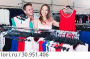 Купить «Wife and husband are choosing dress for her», фото № 30951406, снято 11 апреля 2017 г. (c) Яков Филимонов / Фотобанк Лори