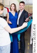 Купить «positive couple choosing new dress in shop with help of female seller», фото № 30951414, снято 11 апреля 2017 г. (c) Яков Филимонов / Фотобанк Лори