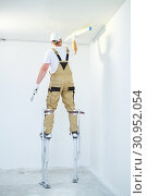 Painter in stilts with putty knife. Plasterer smoothing ceiling surface at home renewal. Стоковое фото, фотограф Дмитрий Калиновский / Фотобанк Лори