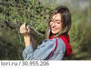 Young girl near the conifer tree's branch. Стоковое фото, фотограф Art Konovalov / Фотобанк Лори