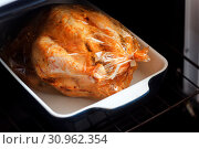 Купить «Appetizing baked chicken with golden roasted crust cooked in the oven in a film sleeve.», фото № 30962354, снято 4 мая 2018 г. (c) easy Fotostock / Фотобанк Лори