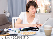 Купить «Woman sitting at table at home calculating domestic finances and bills», фото № 30968510, снято 19 июня 2019 г. (c) Яков Филимонов / Фотобанк Лори