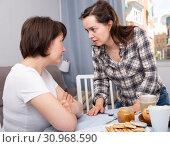 Купить «Upset adult woman quarrel with female friend at table with cookies», фото № 30968590, снято 19 июня 2019 г. (c) Яков Филимонов / Фотобанк Лори