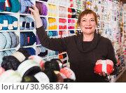Купить «Female client is buying colorful yarn for their hobby», фото № 30968874, снято 10 мая 2017 г. (c) Яков Филимонов / Фотобанк Лори
