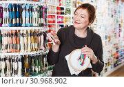 Купить «Woman choosing mouline for embroidery in needlework shop», фото № 30968902, снято 10 мая 2017 г. (c) Яков Филимонов / Фотобанк Лори
