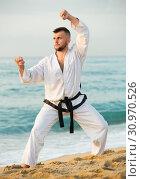Купить «Adult male practising karate kata poses», фото № 30970526, снято 19 июля 2017 г. (c) Яков Филимонов / Фотобанк Лори