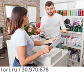 Woman talking with guy specialist about services at beauty salon. Стоковое фото, фотограф Яков Филимонов / Фотобанк Лори