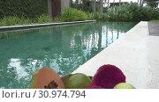 Купить «Tropical fruit and coco at the pool in the tropical resort», видеоролик № 30974794, снято 15 июня 2009 г. (c) Куликов Константин / Фотобанк Лори