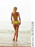 Beautiful young girl with a slim perfect sexy body is standing on the beach by the sea in yellow bikini swimsuit. Стоковое фото, фотограф katalinks / Фотобанк Лори
