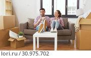 Купить «happy couple drinking coffee moving to new home», видеоролик № 30975702, снято 10 июня 2019 г. (c) Syda Productions / Фотобанк Лори