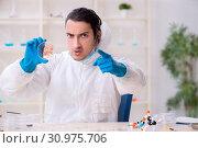 Купить «Young male chemist working in the lab», фото № 30975706, снято 19 апреля 2019 г. (c) Elnur / Фотобанк Лори