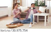 Купить «couple with wine and takeaway pizza at home», видеоролик № 30975754, снято 10 июня 2019 г. (c) Syda Productions / Фотобанк Лори