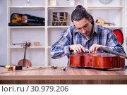 Купить «Young handsome repairman repairing cello», фото № 30979206, снято 4 апреля 2019 г. (c) Elnur / Фотобанк Лори