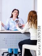 Купить «Young pregnant woman visiting experienced doctor gynecologist», фото № 30979558, снято 11 марта 2019 г. (c) Elnur / Фотобанк Лори
