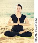 Купить «Female in black T-shirt is sitting and practicing pranayama», фото № 30984882, снято 15 мая 2017 г. (c) Яков Филимонов / Фотобанк Лори