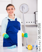 Купить «Female office cleaner is ready to clean the cabinet», фото № 30985058, снято 21 мая 2017 г. (c) Яков Филимонов / Фотобанк Лори