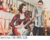 Купить «Charming boy and girl teenagers examining electric guitars», фото № 30985126, снято 14 февраля 2017 г. (c) Яков Филимонов / Фотобанк Лори