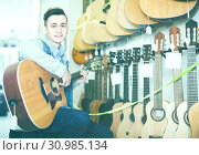 Купить «Smiling male teenager customer deciding on acoustic guitar», фото № 30985134, снято 14 февраля 2017 г. (c) Яков Филимонов / Фотобанк Лори