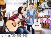 Купить «Teenagers examining guitars in shop», фото № 30985146, снято 14 февраля 2017 г. (c) Яков Филимонов / Фотобанк Лори