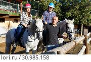 Купить «Positive mature couple with jockey learn to riding horse at farm», фото № 30985158, снято 4 июля 2018 г. (c) Яков Филимонов / Фотобанк Лори