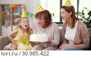 Купить «mother, daughter, grandmother with birthday cake», видеоролик № 30985422, снято 14 июня 2019 г. (c) Syda Productions / Фотобанк Лори
