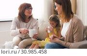 Купить «mother, daughter and grandmother having tea party», видеоролик № 30985458, снято 14 июня 2019 г. (c) Syda Productions / Фотобанк Лори