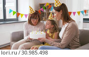 Купить «mother, daughter, grandmother with birthday cake», видеоролик № 30985498, снято 14 июня 2019 г. (c) Syda Productions / Фотобанк Лори
