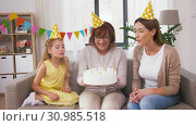 Купить «mother, daughter, grandmother with birthday cake», видеоролик № 30985518, снято 14 июня 2019 г. (c) Syda Productions / Фотобанк Лори