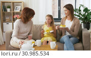 Купить «mother, daughter and grandmother eating cake», видеоролик № 30985534, снято 14 июня 2019 г. (c) Syda Productions / Фотобанк Лори