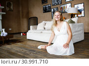Купить «Portrait of a beautiful long-haired pregnant blonde, gracefully sitting on floor», фото № 30991710, снято 15 декабря 2019 г. (c) Ирина Мойсеева / Фотобанк Лори