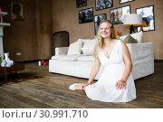 Купить «Portrait of a beautiful long-haired pregnant blonde, gracefully sitting on floor», фото № 30991710, снято 19 июля 2019 г. (c) Ирина Мойсеева / Фотобанк Лори