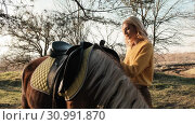 Sad blonde woman is preparing for thr horseback riding with puttin the saddle on the horse's back slow motion. Стоковое видео, видеограф Denis Mishchenko / Фотобанк Лори