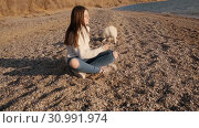 Young girl sits on the baech and observe how her shiba inu pet is sniffin sand slow motion. Стоковое видео, видеограф Denis Mishchenko / Фотобанк Лори