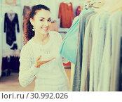 Купить «Brunette choosing skirt in shop», фото № 30992026, снято 28 февраля 2020 г. (c) Яков Филимонов / Фотобанк Лори