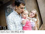 Купить «Tender family hugs. Mom, dad and daughter enjoy each other, girl playing a pipe», фото № 30992410, снято 16 июля 2019 г. (c) Ирина Мойсеева / Фотобанк Лори