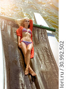 Young beautiful slim sexy girl in bikini and pareo is resting and sunbathe. Стоковое фото, фотограф katalinks / Фотобанк Лори