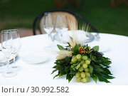 Купить «Table setting for a romantic dinner. Bouquet with bunches of grapes ,laurel leaves», фото № 30992582, снято 25 июля 2017 г. (c) Ирина Мойсеева / Фотобанк Лори
