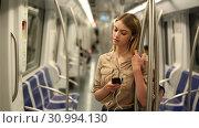 Купить «Young woman with a smartphone and headphones enters a subway car», видеоролик № 30994130, снято 31 марта 2019 г. (c) Яков Филимонов / Фотобанк Лори