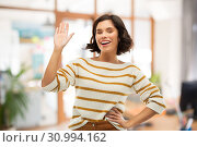 Купить «smiling woman in striped pullover waving hand», фото № 30994162, снято 6 марта 2019 г. (c) Syda Productions / Фотобанк Лори