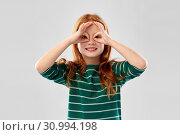 red haired girl looking through finger glasses. Стоковое фото, фотограф Syda Productions / Фотобанк Лори