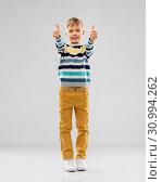 Купить «smiling boy in striped pullover showing thumbs up», фото № 30994262, снято 9 марта 2019 г. (c) Syda Productions / Фотобанк Лори