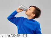 Купить «boy in blue hoodie drinking soda from tin can», фото № 30994418, снято 9 марта 2019 г. (c) Syda Productions / Фотобанк Лори