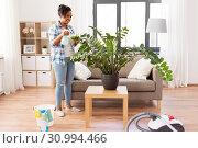 Купить «happy african woman spraying houseplants at home», фото № 30994466, снято 7 апреля 2019 г. (c) Syda Productions / Фотобанк Лори