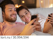 Купить «happy couple using smartphones in bed at night», фото № 30994594, снято 5 января 2019 г. (c) Syda Productions / Фотобанк Лори